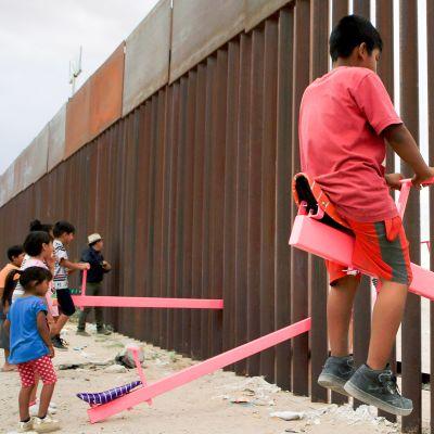 Yhdysvaltalaiset ja meksikolaiset perheet keinuvat keinulaudoilla, jotka on kiinnitetty maiden väliseen raja-aitaan.