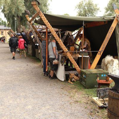 Seppä takomassa metallista esinettä Hämeenlinnan keskiaikfetivaaleilla kojunsa vieressä.