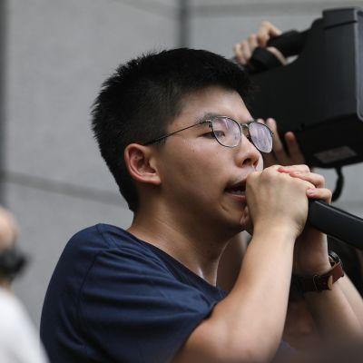 Demokratia-aktivisti Joshua Wong puhui Wanchain poliisiaseman edustalla Hongkongissa 21. kesäkuuta 2019.