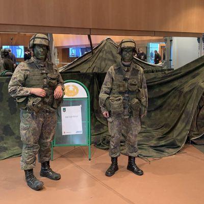 Kaksi sotilasta pukeutuneena maasto-asuun