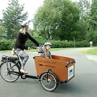 Perhepäivähoitaja Minna Kettunen kuljetti lastipyörällä parhaimmillaan neljää lasta kerrallaan. Laatikossa on turvavyöt neljälle lapselle.