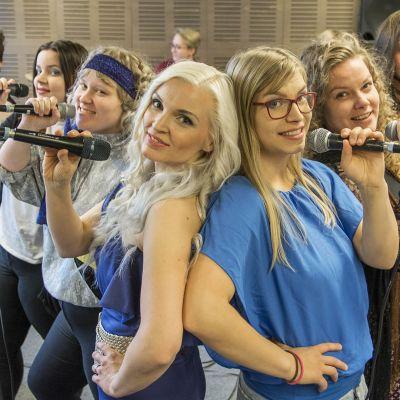 Seitsemän opiskelijaa poseeraa mikrofonien kanssa