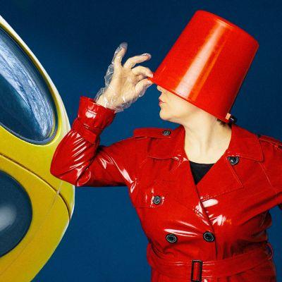 Futuro-muovitalo ja henkilö, jolla ämpäri päässä ja punainen lateksitakki
