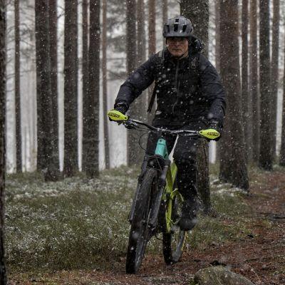 Aku Partanen ajaa maastopyörällä metsäpolulla, ja taivaalta ripottelee rännänsekaista lunta.