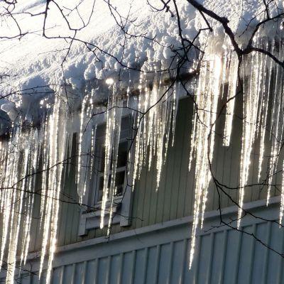 Istappat hänger från kanten av ett snöigt tak