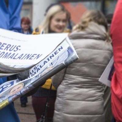 Pesussuomalaisten jäsen jakaa puolueen mainoslehteä Myyrmäen torilla.