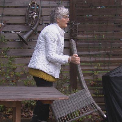 Margita Vainio plockar undan trädgårdsmöbler inför vintern