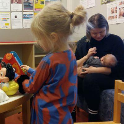 Tyttö leikkii nukella neuvolan odotustilassa. Äitillä on taustalla vauva sylissään.