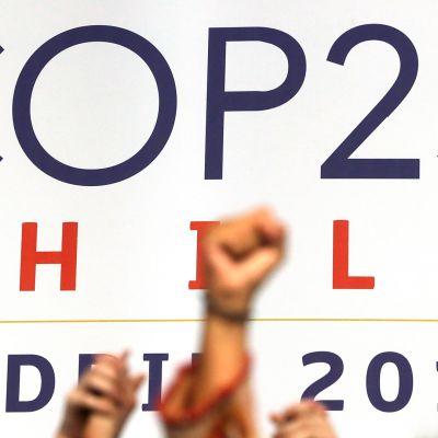 Konferenssiin osallistuvien nyrkkejä ilmassa lähikuvassa YK:n ilmastokokouksen lavalla.