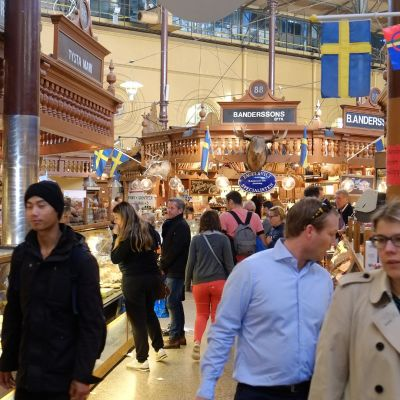 Tukholmalaisia ostoksilla Östermalm kauppahallissa.