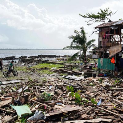 Alueen asukkaat kulkivat taifuuni Phanfonen pahoin turmelemalla rannalla Taclobanissa 25. joulukuuta.