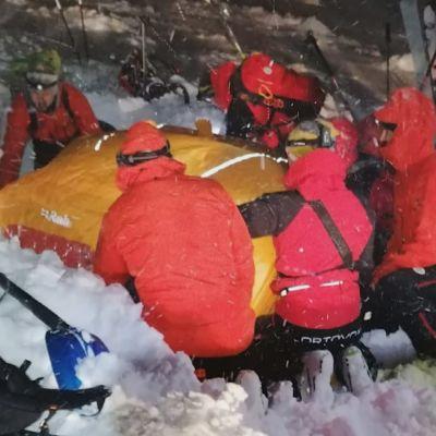 Österrikiska räddningsarbetare hjälper en man som begravdes i ett snöskred.