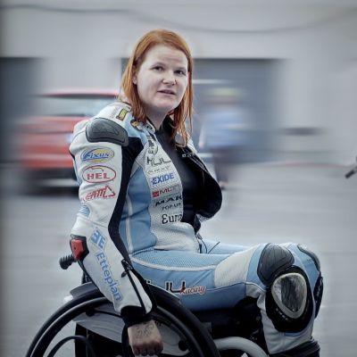 Ulla Kulju istuu pyörätuolissa ajovarusteet päällään Kymiringillä moottoripyöränsä vieressä.