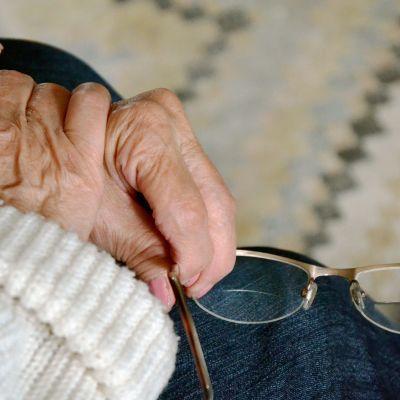 Vanhemman naisen kädet lähikuvassa, silmälasit kädessä.