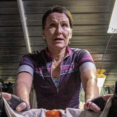 Nainen polkee kuntopyörää hikisenä kellarissa.