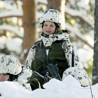 Naisalokkaita lumihangessa ampumaharjoituksissa.