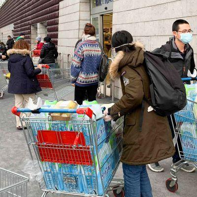 Ihmiset jonottavat ostoksille supermarkettiin Milanossa.