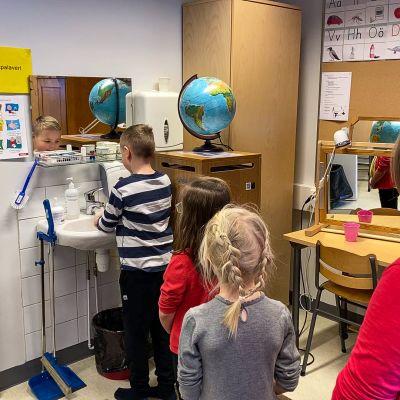 Koululaiset jonottavat käsien pesulle.