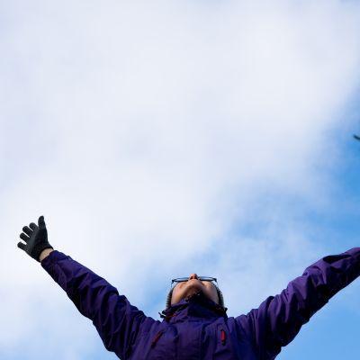 Nainen venyttelee ja kurottaa kohti taivasta.