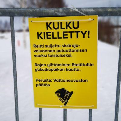 Rajapuomi ja Kulku kielletty-kyltti Suomen ja Ruotsin rajalla Torniossa, tulvavallin päällä. Puomin takana Ruotsin Haaparanta.