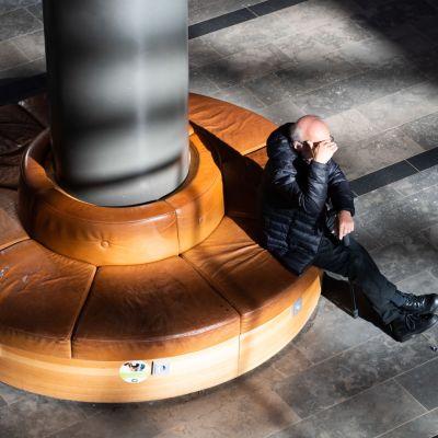Vanha mies istuu kauppakeskuksen penkillä.