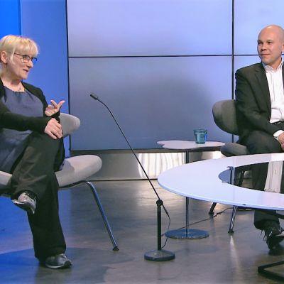 Kvinna och man sitter i tv-studio och diskuterar.
