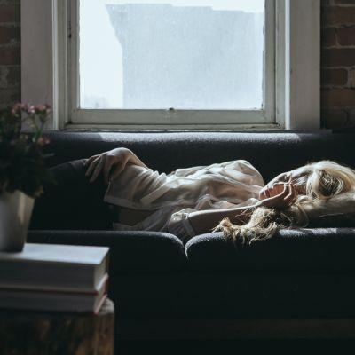 Nainen makaamassa sohvalla.