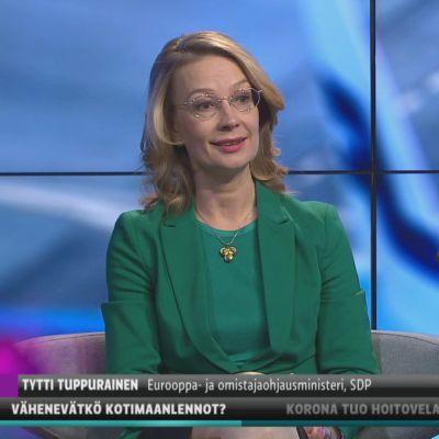 Europa- och ägarstyrningsminister Tytti Tuppurainen klädd i grönt ser in i kamera och ler. Hon sitter i Yles tv-studio där bakgrunden är blå och abstrakt.