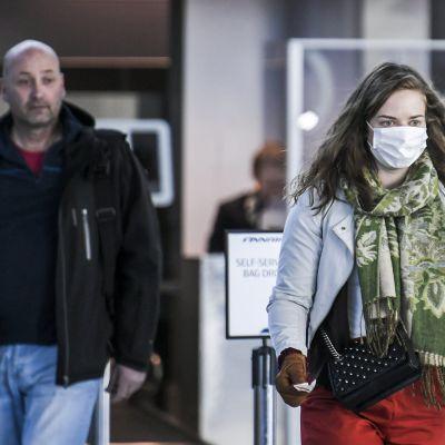 Suu- ja nenäsuojainta käyttävä matkustaja Helsinki-Vantaan lentokentällä.