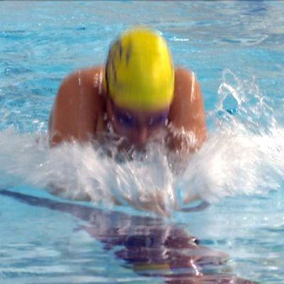 En simmare iförd gul simmössa och simglasögon.