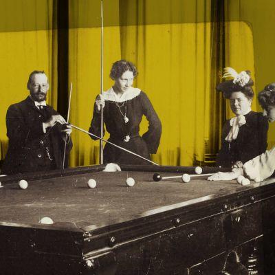 Kuvassa kolme naista ja yksi mies pelaavat biljardia 1800-luvulla.