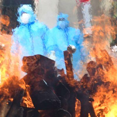 Suojapukuihin pukeutuneita terveyhoitohenkilökuntaa seisoo liekkien taustalla menehtyneiden uhrien hautajaisissa.