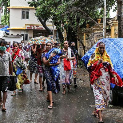 Kalastajayhteisön asukkaita kävelevät kohti väliaikaista suojaa Nisarga syklonin lähestyessä.