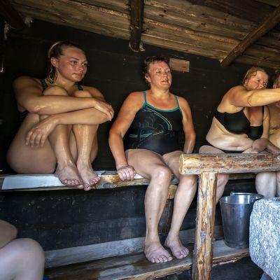 Eri-ikäisiä ihmisiä savusaunassa Jämsän Saunakylässä