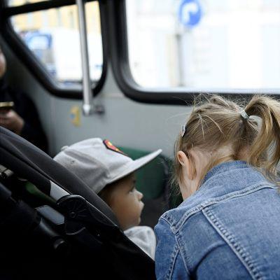 Kasvomaskeja käyttävä perhe julkisessa liikenteessä Helsingissä 12. elokuuta.