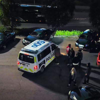 Poliisiauto on pysähtynyt toisten autojen viereen.