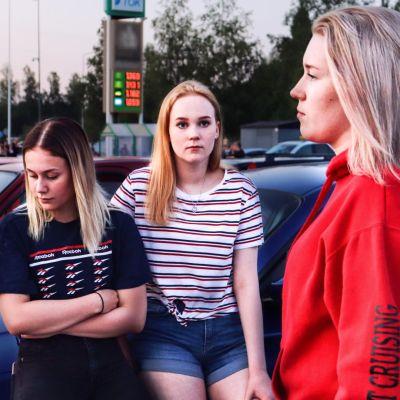 Kolme nuorta naista henkilöauton edessä kesäiltana.