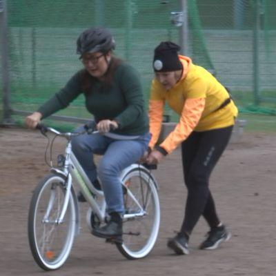 Nainen ajaa pyörällä, jota toinen nainen tukee.
