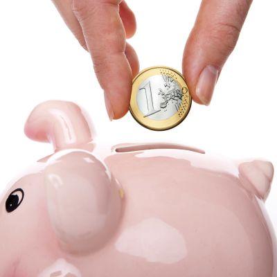 Käsi laittaa rahaa säästöpossuun.