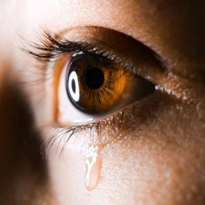 Silmä, josta valuu kyynel.
