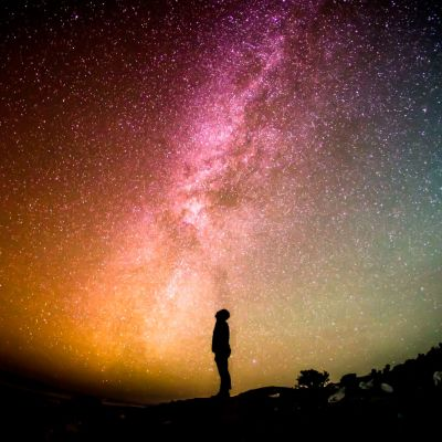 Ihmishahmo katsoo kohti tähtitaivaan upeita värejä.