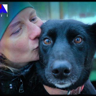 Nainen pussaa mustaa koiraa lähikuvassa.