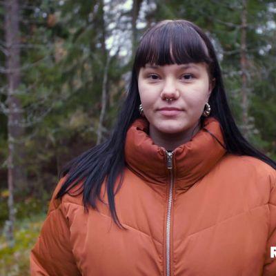 Puolikuva Annasta, joka katsoo kameraan. Annalla on oranssi toppatakki ja mustat pitkät hiukset.