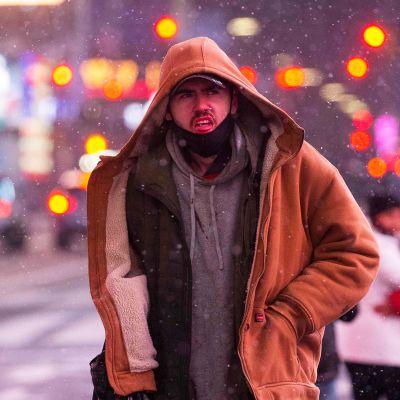 Ihmisiä lumisateessa New Yorkin Times Squarella.