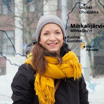 Saamelainen Laura Feodoroff seisoo ulkona Helsingissä talvivaatteet päällään. Taustalla näkyy kartta Pohjois-Suomesta.