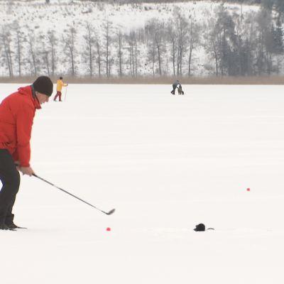 Mies pelaa golfia jäällä.