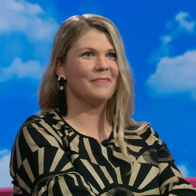 laulaja Katri Ylander istuu Puoli seitsemän -ohjelman pinkillä sohvalla.