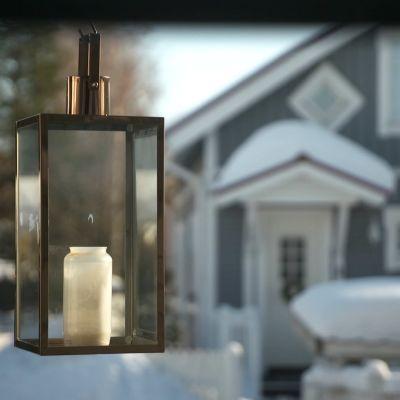 Kynttilälyhty omakotitalon terassilla, taustalla sininen puutalo, jonka katolla paljon lunta.