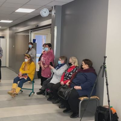 Oppilaat istuvat portailla ja paltamolaiset naiset istuvat tuoleilla