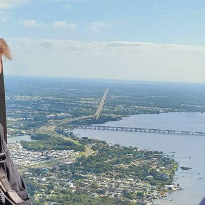 En man med hörselskydd ser ner på ett land och vattenområde från en helikopter.